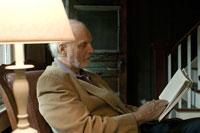 窓際で本を読むシニア男性