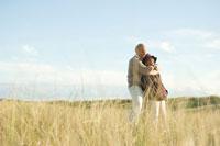 草原で抱き寄せ合うシニアカップル 24007000856A  写真素材・ストックフォト・画像・イラスト素材 アマナイメージズ
