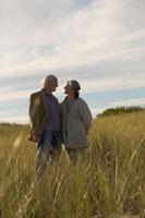 草原で見つめ合うシニアカップル