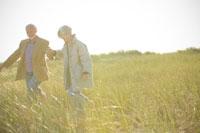 草原を歩くシニアカップル 24007000863| 写真素材・ストックフォト・画像・イラスト素材|アマナイメージズ