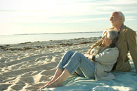 浜辺に座り海を見つめるシニアカップル