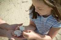 貝殻を手のひらにのせる少女