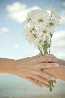 少女に白い花を渡す母親の手元