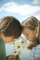 白い花の匂いをかぐ少年と少女