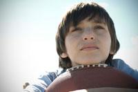 あごをフットボールに乗せる少年