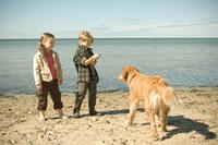 浜辺で犬と遊ぶ少年と少女