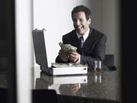 お金を数えながら笑っているビジネスマン