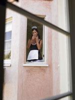 窓辺でタバコを吸うメイド姿の女性