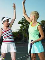 テニスコートでハイタッチをするシニア女性