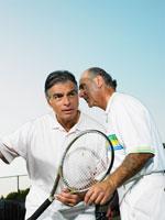 テニスコートで耳打ちするシニア男性