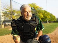 野球場でベースボールを手に持つシニア男性