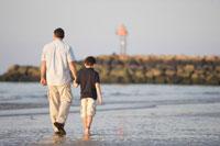 海岸を手を繋いで散歩する父と息子