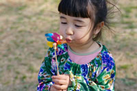 風車を吹いている女の子 24009000045| 写真素材・ストックフォト・画像・イラスト素材|アマナイメージズ