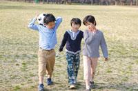 ボールを持って歩いている3人の男の子