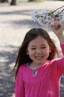 桜の花が咲いた枝を持って笑顔の女の子