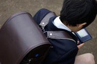 ゲーム機で遊んでいる小学生の男の子
