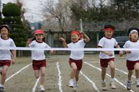運動会のリレーでゴールする直前の小学生
