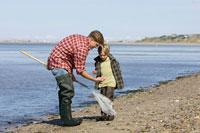 海岸で貝殻を拾う親子 24009000136| 写真素材・ストックフォト・画像・イラスト素材|アマナイメージズ