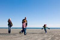 海岸を散歩する老夫婦と傍ではしゃぐ孫たち