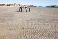 手を繋いで海岸を散歩する老夫婦と孫たち 24009000156  写真素材・ストックフォト・画像・イラスト素材 アマナイメージズ