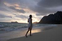 日の出の浜辺で散歩する女性