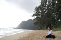 浜辺に犬と座っている女性