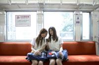 電車で音楽を聴く女子高生