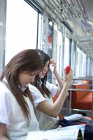 電車で身嗜みをする女子高生