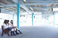 駅のベンチで話す女子高生3人