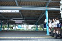 駅でおしゃべりする女子高生3人