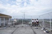 屋上から外を眺める女子高生3人