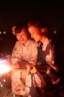 花火をする浴衣姿の女の子2人