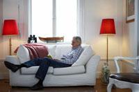 ソファーで読書をするシニア男性