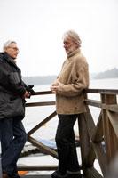 湖の見える場所で話をしているシニア男性二人