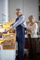 キッチンで妻にエプロンをつけてもらうシニア男性