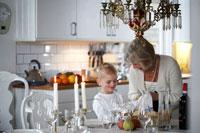 ダイニングテーブルの準備をするシニア女性と男の子