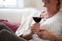 ワイングラスを持ってソファに座るシニア女性 24012000104| 写真素材・ストックフォト・画像・イラスト素材|アマナイメージズ