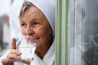 バスローブ姿で水を飲むシニア女性