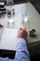 机の上でノートを書いている男性の手