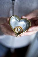 二つの結婚指輪が入ったハート型の入れ物を持つ手 24012000143  写真素材・ストックフォト・画像・イラスト素材 アマナイメージズ
