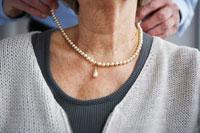 シニア女性にネックレスをつけてあげるシニア男性