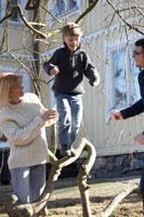 枝の上を歩く息子を支える夫婦