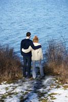 寄り添って湖を眺めるカップル 24012000242| 写真素材・ストックフォト・画像・イラスト素材|アマナイメージズ