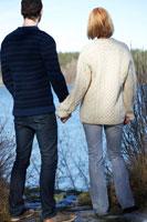 寄り添って湖を眺めるカップル