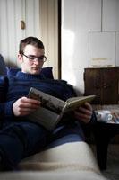 ソファーで本を読んでいる男性