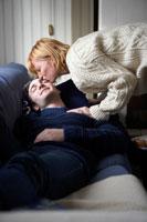 ソファーで寝ている男性にキスをする女性 24012000253| 写真素材・ストックフォト・画像・イラスト素材|アマナイメージズ