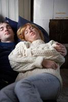 ソファーで一緒に昼寝をするカップル