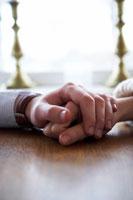 テーブルで手を握り合うカップル