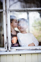 窓際に立って男の子にキスする女の子