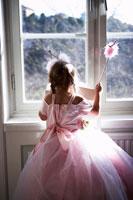 プリンセスのコスチュームで窓の外を眺める娘の後姿